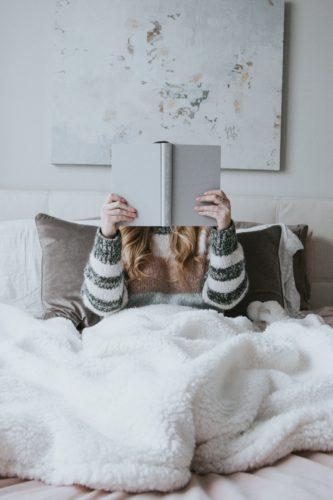 tyttö, kirja, sänky ja peitto